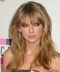 Taylor Swift - Cool and casual is the main idea for this hairstyle. These dark golden blonde locks are left out to fall over the shoulders showing off the jagged cut layers through the back and sides. The bangs are smoothed down to frame the top of the face and completes the over-all look 'do brilliantly. Product is needed for shine and hold.