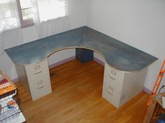 Corner desk from 1 piece of plywood and two file cabinets. Very economical. I love the curves, which makes this not just another boring desk. The judicious use of the plywood makes it all that much better. I'd love to sit at this desk one day.