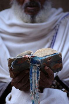 A man reading a printed book with traditional binding in Lalibala. By Keith Levit Photography.