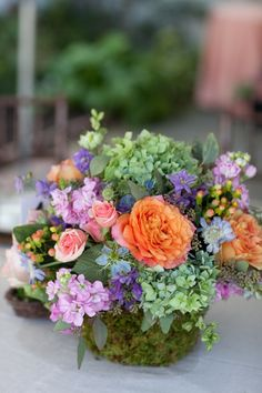 Garden-style centerpiece of spring blooms in a moss-covered vase