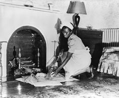 USA c. Photo of an African American woman in domestic servant uniform kneeling in front of a fireplace in a bedroom, cleaning fireplace tools over newspapers laid on floor. Women In History, Black History, American Photo, Black Image, African American History, Black People, Historical Photos, Vintage Photos, The Help