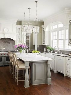 American Classic - Elegant millwork and furniture-like details give this new kitchen the spirit of a historic home. A grand and gracious gray island is at the heart of this kitchen, while white exterior cabinets and slab granite lighten the room's top half #traditionalkitchens