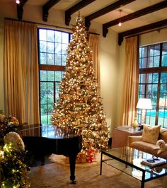 12 ft tree. Lights, gold ribbon, and mercury gold nature-themed glass ornaments.