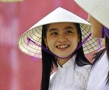 Ao dai - A schoolgirl in a white ao dai and a nón lá (leaf hat). This ensemble is associated with the central city of Huế