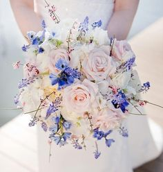 whisper pink roses, white ranunculus and sweet pea with accents of blue muscari and delphinium for a spring bride- designed by Petals and Promises,llc