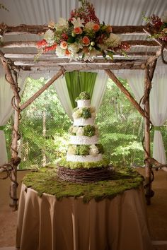 Hydrangea covered wedding cake, moss covered table, and rustic wooden canopy.
