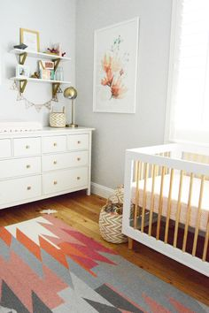 Feminine and fun are the best ways to describe this adorable girl's nursery. Recreate this room design with a colorful aztec rug, pops of coral decor, and modern gold accents!