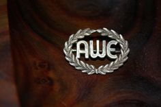 "Shock and ""Awe"" brooch  Lovely Vintage Sterling Monogram Brooch.  The brooch has been designed in a laurel wreath, which encircles an ""AWE"" in script. The laurel wreath is beautifully detailed.  Brooch is unmarked, but likely silver.  Brooch is part of my personal jewelry collection, and is currently for sale!"