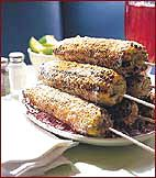 Chile-spiked grilled corn--rolled in cotija cheese