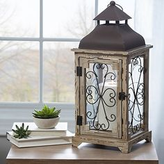 Bring your space to life with our Distressed Cream Antique Scroll Lantern. Its aged design and scrolled panels will add a bold, rustic touch to any space. Wooden Lanterns, Lanterns Decor, Candle Lanterns, Pillar Candles, Brown Lanterns, Candleholders, Recycled Home Decor, Lantern Candle Holders, Diy Lantern