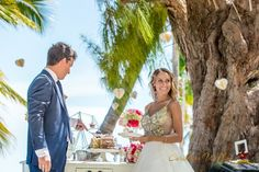 A beautiful picture of the bride and groom sampling some sweet items off their dessert table. Don't you just love the paper hearts that seems to be floating in the air?!?! #weddings #caribbean #dominicanrepublic #destinationwedding #caribbeanweddingagency #weddingincaribbean