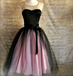 A pink and black womans tulle skirt  has several layers tulle lined in pink satin. You will feel special wearing this classic ballerina skirt as it rustles and swirls on the dance floor. It is a unique garment and you will not find one in a store! The
