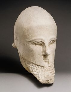 Male head wearing a Greek helmet, Cypriot limestone sculpture, early 5th century BCE. From the collection of the Metropolitan Museum of Art.