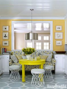Bright yellow walls — Benjamin Moore's Inner Glow — and an even brighter citron table from HB Home brought the white-and-gray kitchen in a Charlotte, North Carolina, house to life. Designer Lindsey Coral Harper turned wire side tables from ABC Carpet & Home into stools. Dark brown floors were transformed with a large geometric pattern, painted by Jay C. Lohmann. Pendant light from Robert Abbey. Hugo Guinness prints from John Derian.