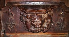 Bagpipe-playing figure on a medieval misericord in Faversham parish church.