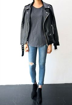 Den Look kaufen: https://lookastic.de/damenmode/wie-kombinieren/bikerjacke-schwarze-t-shirt-mit-rundhalsausschnitt-graues-jeans-hellblaue/18123 — Graues T-Shirt mit Rundhalsausschnitt — Schwarze Leder Bikerjacke — Hellblaue Jeans mit Destroyed-Effekten — Schwarze Wildleder Stiefeletten