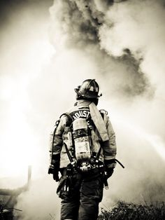 """A Houston firefighter looks on helplessly as smoke billows out from a warehouse fire.    — By Cody Austin (from """"Danger"""")"""