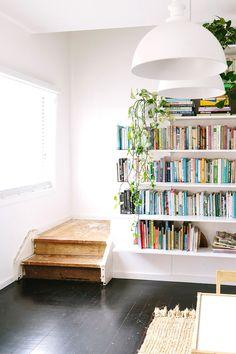 Bookshelf beside small steps of well-worn wood