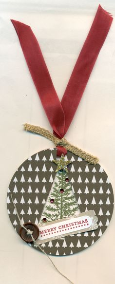 Cased this from our Unite & Excite make & take from Littleton, CO. Festival of Trees stamp and punch, Trim the Tree paper stack and the Circle Framelits. Used wide burlap ribbon cut into strips. colored rhinestones with Blendabilities marker. It is 3 D as the tree is recessed. There is a layer of fun foam (cut by framelits) in between the front and back paper for depth. Cherry Cobbler seam binding. Stampin' Up!