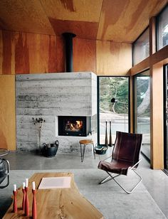 A home at Sea Ranch on the N California coast. The living room is furnished with vintage items, including a leather-and-chrome chair by Suekichi Uchida and a stacking stool by Florence Knoll. Photo by: Mark Mahaney Concrete Fireplace, Fireplace Design, Concrete Floors, Concrete Wood, Modern Fireplace, Fireplace Wall, Minimalist Fireplace, Fireplace Windows, Board Formed Concrete