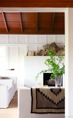 white painted grid paneling, white furniture white fireplace, natural wood…