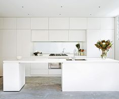 A white laminate kitchen in a matte finish is topped with Caesarstone benchtop. Durable concrete flooring gives warmth to the monochromatic space. Photography: Chris Warnes
