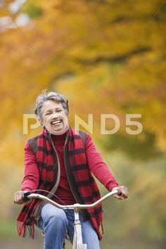 African woman riding bicycle in park in autumn Stock Photos