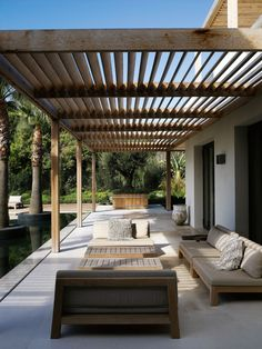 Modern poolside pergola over a concrete patio with minimalist outdoor furniture.