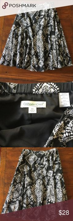 "Coldwater Creek Black with White Skirt Coldwater Creek black skirt white design throughout.  It has a full silky black lining.  May have been worn once and has been cleaned and is just like new.  Material: 100% cotton shell with 100% Polyester liner.  It has elastic on the back side of the waist for the perfect fit.  Measurements: waist unstretched is approx 14""; waist stretched is approx 15""; length is approx 26"".  Size PS Coldwater Creek Skirts Midi"