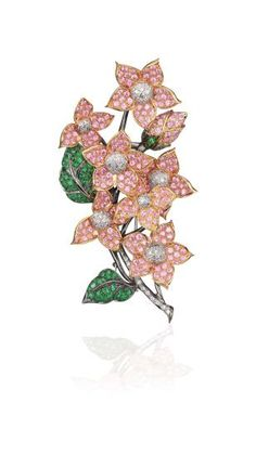 A Pink Sapphire, Tsavorite Garnet, and Diamond Brooch. Designed as a floral spray, each articulated bloom set with circular-cut pink sapphires, centering upon a pavé-set diamond pistil, to the leaves and stem set with circular-cut tsavorite garnets and diamonds, mounted in 18K rose and blackened gold, length 3 1/2 inches.