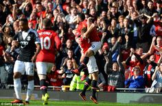 Robin van Persie celebrates his goal by jumping into Michael Carrick's arms