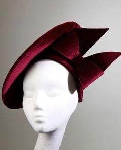 Sherry- A rich velvet burgundy disk, held in place with a burgundy velvet hairband and finished with a large matching architectural bow. Carol Kennelly Millinery