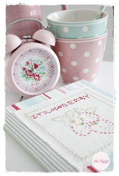 Pink, floral and gingham alarm clock, strawberry embroiderd fabric book, and pastel polka dot bowls.
