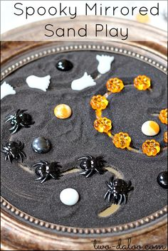 An open-ended invitation to play with black sand on a mirror and Halloween-themed loose parts.