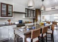 Beautifully appointed cottage kitchen boasts woven fabric counter stools placed in front of a gorgeous gray wash freestanding island illuminated by two polished nickel dome light pendants hung from a white rustic plank ceiling.