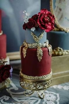 Burgundy and gray cake with big red blossoms and molded gold details.