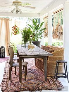 Bohemian style doesn't have to be extremely colorful. When the right elements are collected and layered correctly, even a mix of brown hues can evoke an artistic vibe. Weathered wood and tan tones dominate this Bohemian dining space. An old rug features hints of pink and orange, and plants provide freshness./