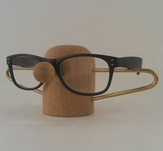 Elegant and practical eyeglass holder with a humorous twist. Perfect for the bathroom or your night stand. Handmade from solid oak, with a brass tube.