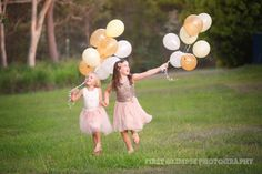 Sisters running with helium balloons - gold, yellow and white. Great sibling photo.