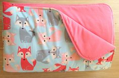 This large baby blanket is sure to keep your little one warm! The top is a fox patterned soft minky and the bottom is a coral pink 100% cotton. There