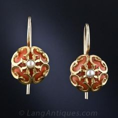 A pair of orangy coral half-beads reside in fanciful 14 karat golden cages, crowned with a shimmering seed pearl, in these rather unusual and quite delightful Victorian-era earrings on simple ear wires. 7/16 inch diameter.