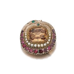 A GEM-SET BROOCH, EARLY 19TH CENTURY $ 2,250.00 Set at the centre with a foiled topaz within a border designed as two coiled snakes highlighted with graduated seed pearls and circular-cut foiled back garnets, later brooch fitting.