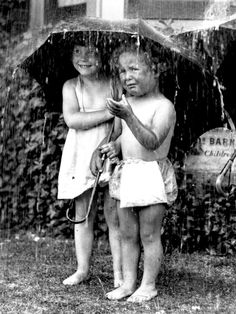 kids under umbrella in the rain.