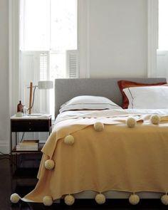 Easy upgrade: oversize pom-poms threaded onto a blanket | Martha Stewart