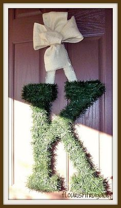 Cut out your family initial from wood (or go to a craft store and buy a large letter of your last name).  Wrap it in garland for your front door!  So cute!