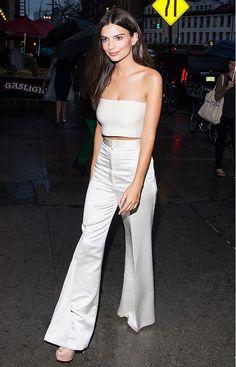 Emily Ratajkowski wears a crop top, high-waisted white satin trousers, and platform heels