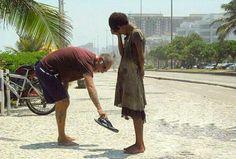 Uma foto de um homem dando seus chinelos para uma moradora de rua no Rio de Janeiro.