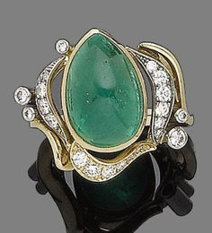 An emerald and diamond dress ring Of bi-coloured design, the pear-shaped cabochon emerald, within an openwork stylised surround set with graduated brilliant-cut diamonds, diamonds approx. 0.35ct total