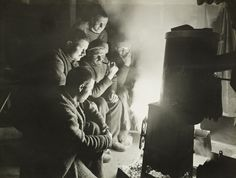Frank Hurley  The night watchman, with little to do, apart from observing ice movements, gathers with the men around the fire to share stories in 1915.
