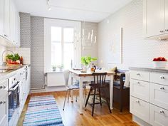 Alternative view of the kitchen in a tiny apartment with chandelier, geometric wallpaper, white cabinets and drawers, a cozy breakfast nook with a bench and mismatched chairs a wood floor and a striped rug by ginaska